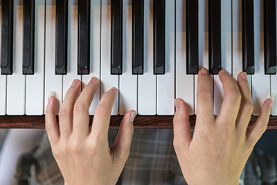 Hands at piano keyboard
